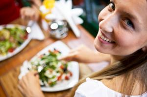 Woman eating with company