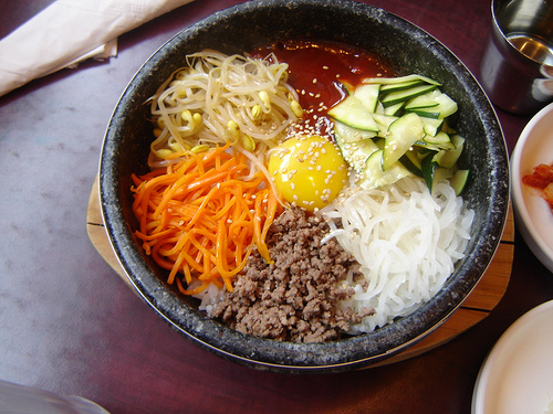Dolsot bibimbap with raw egg is served in a very hot pot