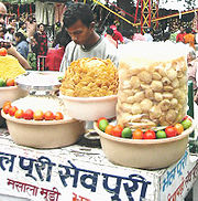 "A young man at his chaat stand in Mussoorie, India. The main text on the front says ""bhel puri"" and ""sev puri"" in Hindi. In the plastic bag are puris for panipuri; the yellow substance is sev; the fried crackers are papdi; the white substance is puffed rice; and the other things are chopped onions, limes and tomatoes."