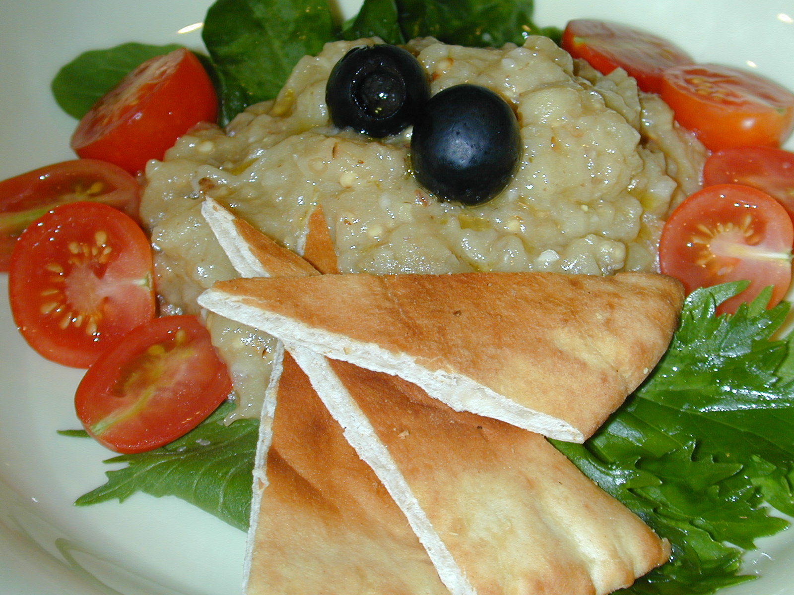 There are several ways of eating Baba Ganouj, here it has been served with bread and vegetable garnish