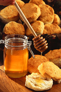 A jar of honey, shown with a wooden honey server and scones/biscuits.
