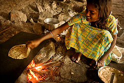 An Indian girl baking chapatis.