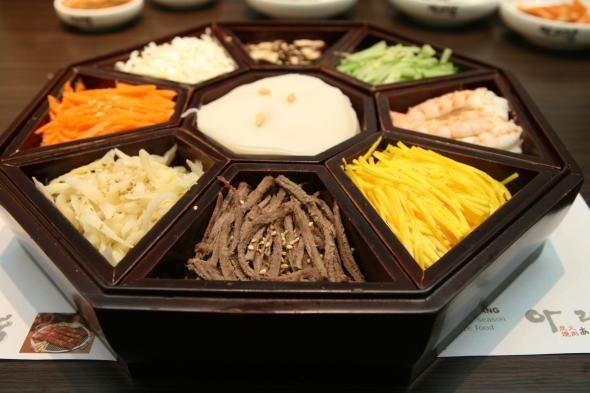 A tray full of garnishments are served along with Janchi Guksu, the diners can build their own soup using these ingredients
