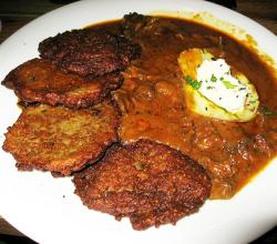 Boarish goulash with potato pancakes and horseradish