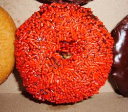 Chocolate-covered doughnut with red sprinkles