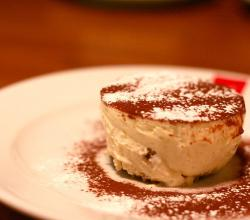 Tiramisu serving with cocoa and powdered sugar