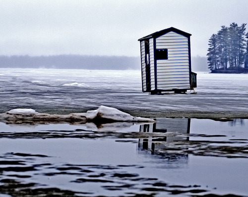 A white homemade ice fishing shanty