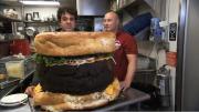 Adam Richman teaches UK Journos how to eat a five-pound hamburger.