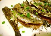 Yummy looking crisp broiled sardines with herbs and lime juice