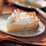 A slice of coconut cream pie with whipped cream topping