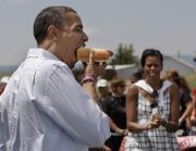Obama gorging on a hot dog as Michelle seems to be looking angry