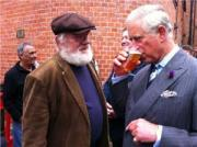 Prince Charles sneaks in a few sips of beer as Sergeant looks on.