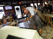 Obama in a bear hug swept off his feet  by pizza shop owner