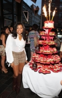 Taraji Henson poses next to layers of cupcakes.