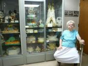 Frances Kuyper sits guard to her cake collection.