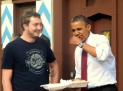 The store manager looks on as Obama enjoys a bratwurst sandwich,