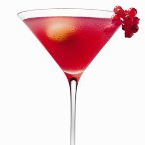 Pomegrante martini drink garnished with fresh fruits.