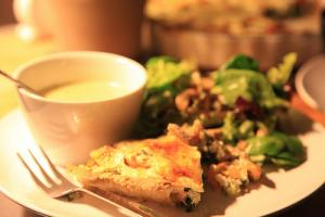 A tempting slice of quiche served with salad and a cup of tea.