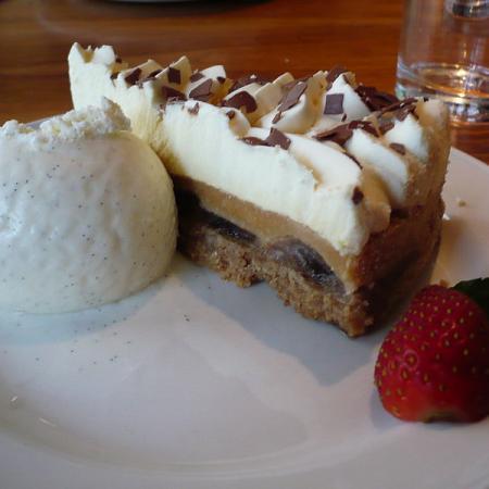 Slice of banoffee pie with vanilla ice cream and strawberries