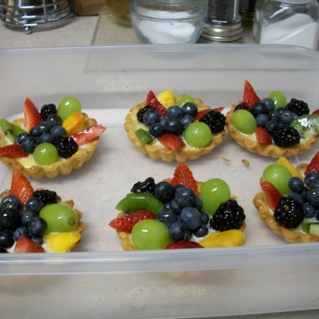 Tarts with lemon curd and seasonal fruits.