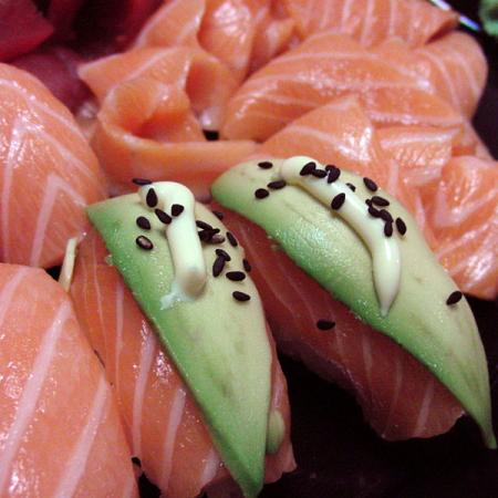 Sushi uramaki salmon with avocado and sesame topping